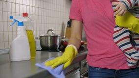 Moeder` s midsection schoonmakende keuken met baby stock videobeelden