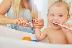 Moeder scherpe spijkers met schaar aan de baby Stock Foto's