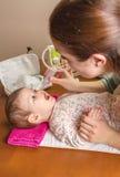 Moeder schoonmakend slijm van baby met neusaspirator Stock Afbeeldingen