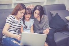 Moeder, Tante en het jonge geitje die de de tijd hebben die samen met het gebruiken van laptop computer thuis lerning met ontspan royalty-vrije stock foto's
