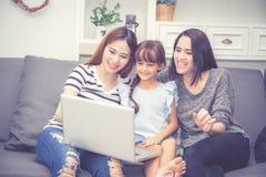 Moeder, Tante en het jonge geitje die de de tijd hebben die samen met het gebruiken van laptop computer thuis lerning met ontspan stock foto's