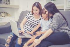 Moeder, Tante en het jonge geitje die de de tijd hebben die samen met het gebruiken van laptop computer thuis lerning met ontspan stock afbeeldingen
