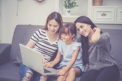 Moeder, Tante en het jonge geitje die de de tijd hebben die samen met het gebruiken van laptop computer thuis lerning met ontspan royalty-vrije stock afbeelding