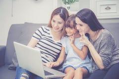 Moeder, Tante en het jonge geitje die de de tijd hebben die samen met het gebruiken van laptop computer thuis lerning met ontspan royalty-vrije stock afbeeldingen