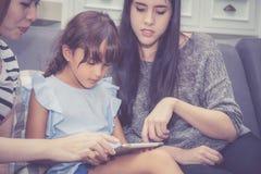 Moeder, Tante en het jonge geitje die de de tijd hebben die samen met het gebruiken van tablet thuis lerning met ontspannen en ge royalty-vrije stock afbeeldingen