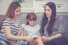 Moeder, Tante en het jonge geitje die de de tijd hebben die samen met het gebruiken van tablet thuis lerning met ontspannen en ge royalty-vrije stock afbeelding