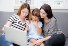 Moeder, Tante en jong geitje die tijd hebben die samen met thuis het gebruiken van laptop op laag, familieconcept lerning stock afbeelding
