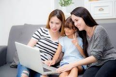 Moeder, Tante en jong geitje die tijd hebben die samen met thuis het gebruiken van laptop op laag lerning royalty-vrije stock afbeelding