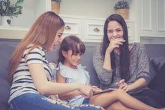 Moeder, Tante en jong geitje die tijd hebben die samen met thuis het gebruiken van tablet lerning stock foto's