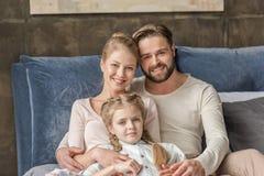 Moeder, vader en dochter die en camera thuis koesteren bekijken royalty-vrije stock afbeeldingen