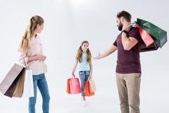 Moeder, vader en dochter die zich met het winkelen zakken bevinden royalty-vrije stock fotografie
