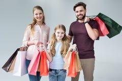 Moeder, vader en dochter die zich met het winkelen zakken bevinden stock foto's
