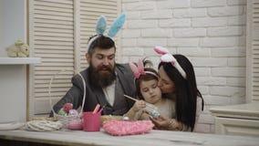 Moeder, vader en kind het meisje schildert paaseieren De gelukkige familie treft voor Pasen voorbereidingen Leuk weinig kindmeisj stock video