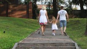Moeder, vader, weinig dochtergang in de zomerpark, achtermening stock video