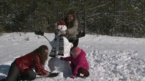 Moeder van het hurken naast dochter en sneeuwman stock footage