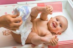 Moeder veranderende luier aan haar weinig babymeisje Royalty-vrije Stock Afbeelding
