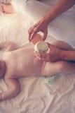 Moeder veranderende luier haar weinig baby op het bed Royalty-vrije Stock Foto