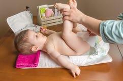Moeder veranderende luier van aanbiddelijke baby Stock Afbeeldingen
