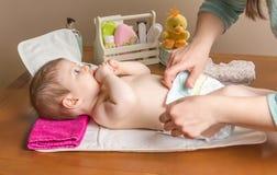 Moeder veranderende luier van aanbiddelijke baby Royalty-vrije Stock Afbeelding