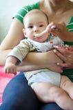 Moeder voedende baby, babyzuigeling die van lepel eten Stock Fotografie