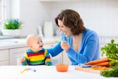 Moeder voedende baby eerste stevig voedsel stock foto