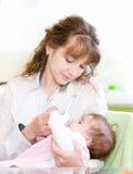 Moeder voedende baby met het voeden van fles in keuken Royalty-vrije Stock Afbeelding