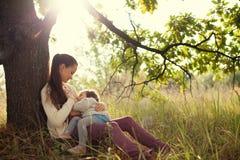 Moeder voedende peuter in openlucht Royalty-vrije Stock Foto's
