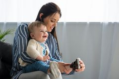 moeder vrolijk kleden zich weinig baby op bank royalty-vrije stock afbeeldingen