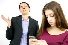 Moeder wanhopig over de verslaving van de dochtertelefoon Stock Foto's
