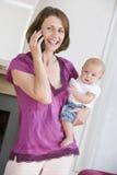 Moeder in woonkamer die de baby van de telefoonholding gebruikt Stock Fotografie