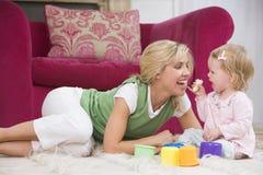 Moeder in woonkamer met baby die banaan eet Royalty-vrije Stock Afbeeldingen