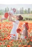 Moeder, zoon en dochter op een gebied van rode papavers royalty-vrije stock fotografie