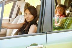 Moederbestuurder en meisje in de zetel van de autoveiligheid Stock Foto's