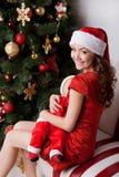 Moederborst - voedende baby in Kerstman` s kostuums Royalty-vrije Stock Afbeeldingen