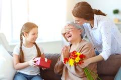 Moederdag! drie generaties van familiemoeder, grootmoeder en dochter wensen met de vakantie geluk, geven bloemen stock afbeeldingen