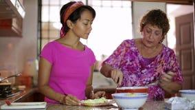 Moederdochter die maaltijd samen in keuken voorbereiden stock footage
