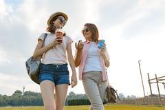 Moederdochter die op het gazon in het park, de verhouding tussen ouder en kindtiener lopen, zonnige de zomerdag stock afbeeldingen