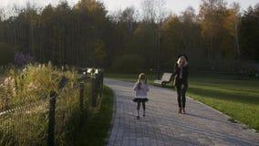 Moedergangen met dochter in het Park bij zonsondergang Lichte lekken Het weer van de herfst Houten gang Kind en ouder in een de z stock video