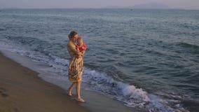 Moedergangen met haar dochter langs de kust van het overzees stock footage