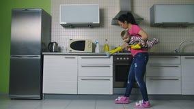 Moederholding baby en het schoonmaken keukenoppervlakten stock videobeelden