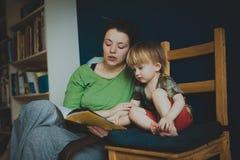 Moederlezing met haar toevallige zoon thuis, Royalty-vrije Stock Foto
