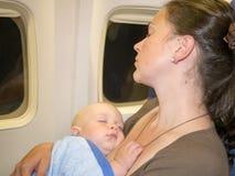 Moederomhelzing en slaap met haar pasgeboren baby tijdens vlucht Conceptenfoto van luchtreis Royalty-vrije Stock Foto's