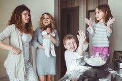 Moeders die met kinderen koken Stock Foto's
