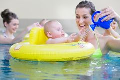 Moeders en jonge geitjes die pret hebben die samen met speelgoed in pool spelen Stock Afbeeldingen