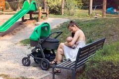 Moederschap, jong wijfje die haar baby in openbare, gevende baby in haar wapens en het voeden met moeder` s melk de borst geven,  stock fotografie