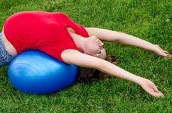 Moederschapsyoga het uitrekken zich op blauwe bal Stock Afbeeldingen