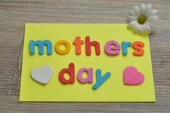 Moedersdag op een gele nota met een wit en roze hart en een margriet Stock Foto