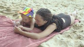 Moederspelen met weinig dochter die smartphone op het strand gebruiken stock footage