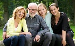 Moedervader en twee dochters die in openlucht glimlachen royalty-vrije stock foto's