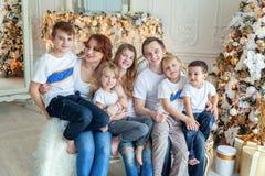 Moedervader en vijf kinderen dichtbij Kerstboom thuis stock afbeeldingen